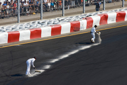 Corner workers clean up the track after the crash at the start