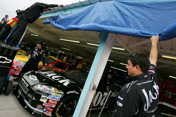 Crew members for the #07 Jack Daniel's Chevrolet, driven by Casey Mears, cover the garage opening due to impending rain