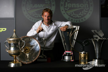 Jenson Button celebrates 2009 world championship with his race victory trophies