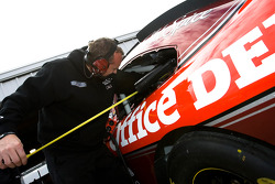 A crew member for the Office Depot crew makes adjustments to car