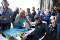Fernando Alonso, McLaren, takes a picture for a fan