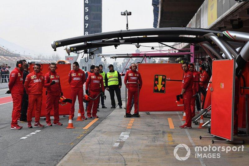 Mecánicos de Ferrari con paneles para tapar su coche de la vista de los curiosos