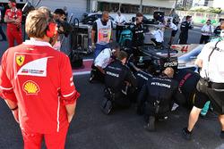Ingeniero de Ferrari observa el coche de Lewis Hamilton, Mercedes AMG F1 W08