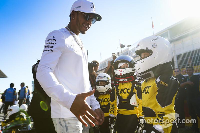 Гонщик Mercedes AMG F1 Льюис Хэмилтон и юные картингисты