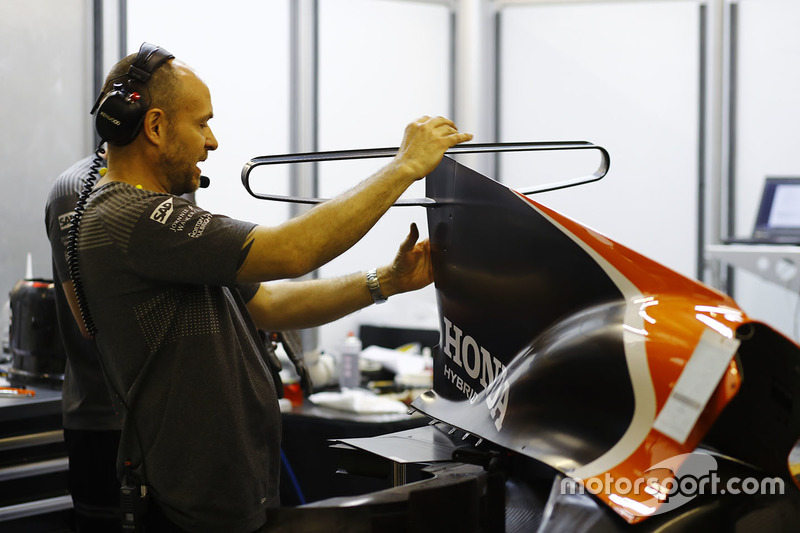 A McLaren team member works on an engine cover