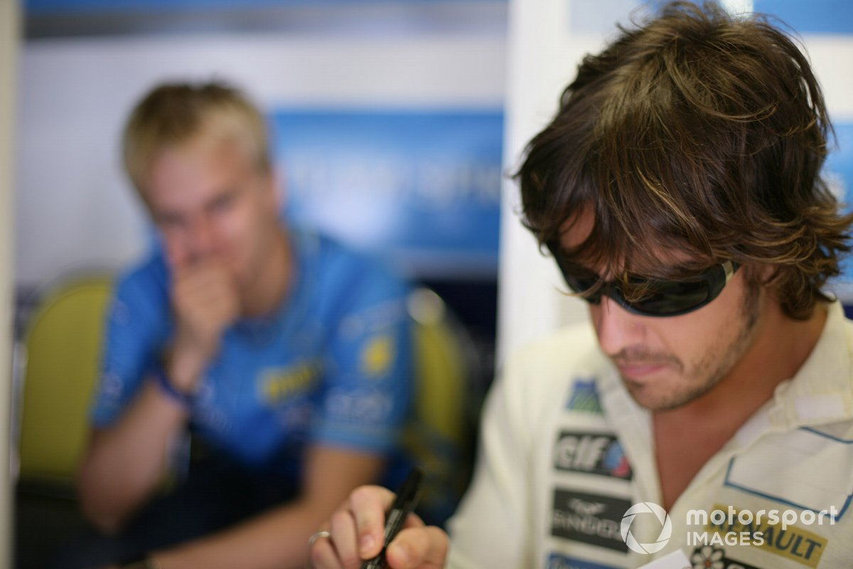 Fernando Alonso, Renault, with team mate and test driver, Heikki Kovalainen in the background