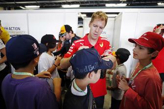 A young fan has a cap signed by Sebastian Vettel, Ferrari.