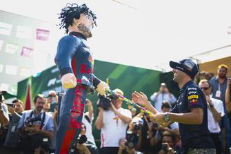 Daniel Ricciardo, Red Bull Racing, hits an impersonator with stick