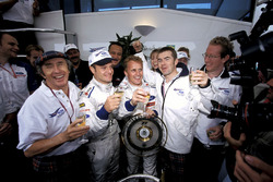 Jackie Stewart, Paul Stewart, and the Stewart team celebrate their first win for Johnny Herbert, and third place for Rubens Barrichello