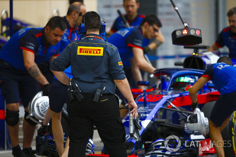 A Pirelli engineer watches as Toro Rosso engineers move Brendon Hartley, Toro Rosso STR13 Honda, to the garage