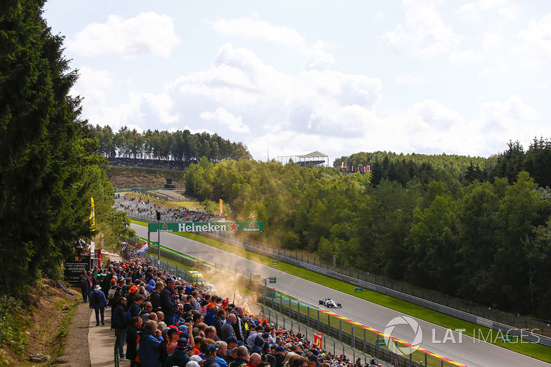 Charles Leclerc, Sauber C37, passes an orange flare and spectators