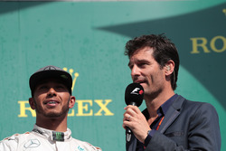 (L to R): Lewis Hamilton, Mercedes AMG F1 on the podium with Mark Webber, Porsche Team WEC Driver / Channel 4 Presenter