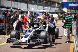 Mechanics push the newly-liveried car of Kevin Magnussen, Haas F1 Team VF-17, in the pits