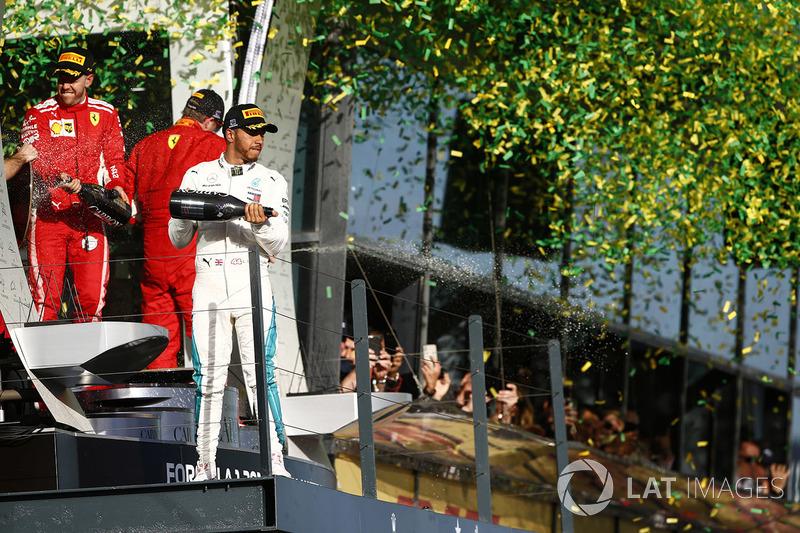 Lewis Hamilton, Mercedes AMG F1, 2nd position, Sebastian Vettel, Ferrari, 1st position, and Kimi Raikkonen, Ferrari, 3rd position, celebrate on the podium with Champagne