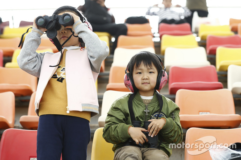 Young fans watch the activity with Binoculars