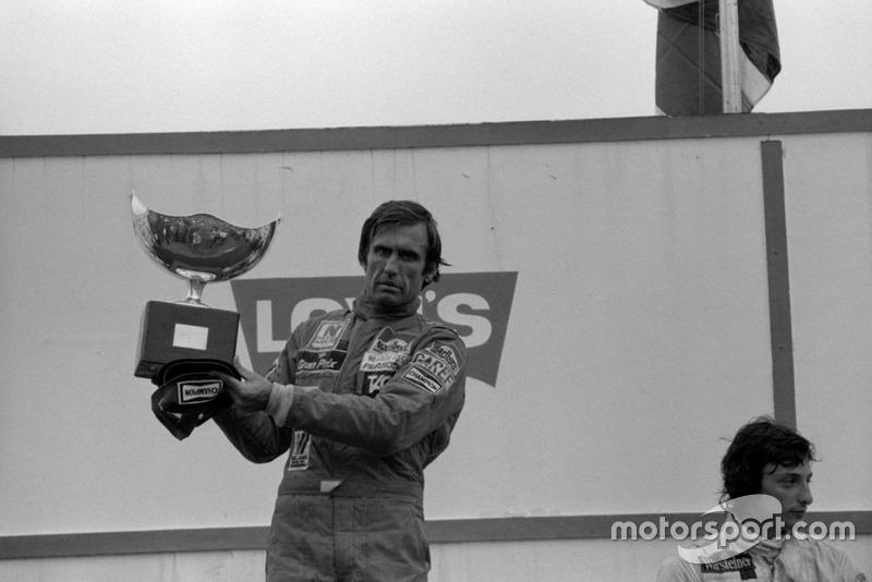 Ganador de la carrera Carlos Reutemann, Williams (Izquierda) con una celebración silenciosa en el podio con Riccardo Patrese en tercer lugar, Arrows (derecha). Carlos no pudo observar las órdenes del equipo dadas durante la carrera para dejar pasar a su compañero de equipo Alan Jones. Jones se negó a aparecer en el podio por ello