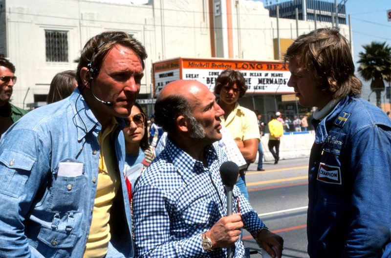 Dan Gurney, a consultant for the GPALB, stands by as friend and former rival Stirling Moss interviews Ronnie Peterson before the '76 race.