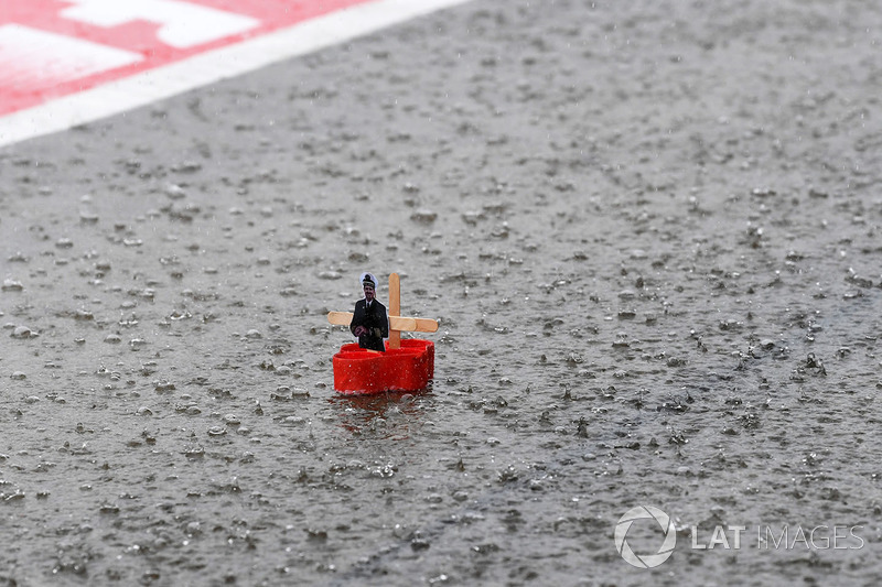 Paper boat floats in a flooded pit lane