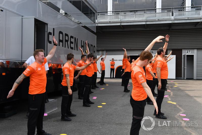 McLaren mecánicos hacen ejercicios de calentamiento