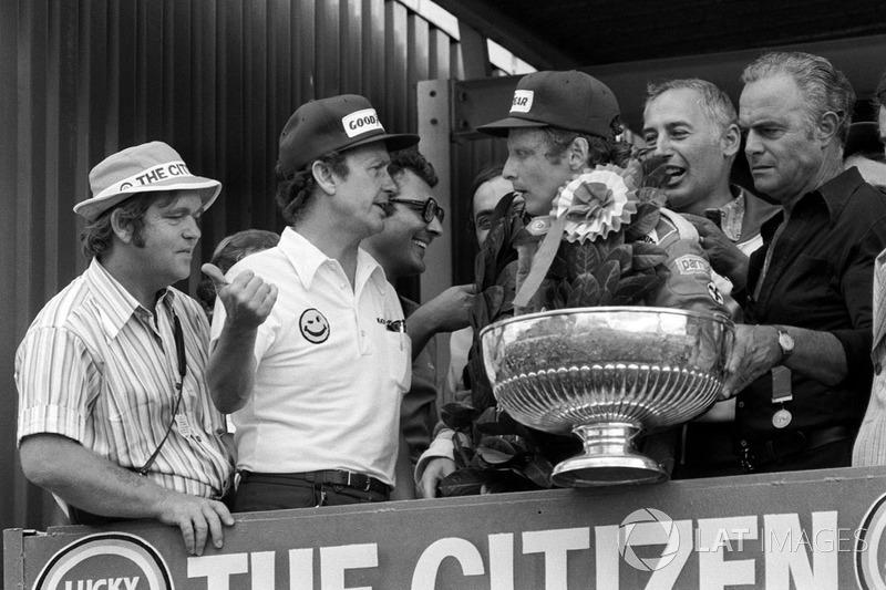 Podio: Bert Baldwin, Goodyear informa al ganador de la carrera Niki Lauda, Ferrari del trágico accidente fatal sufrido por Tom Pryce, Shadow