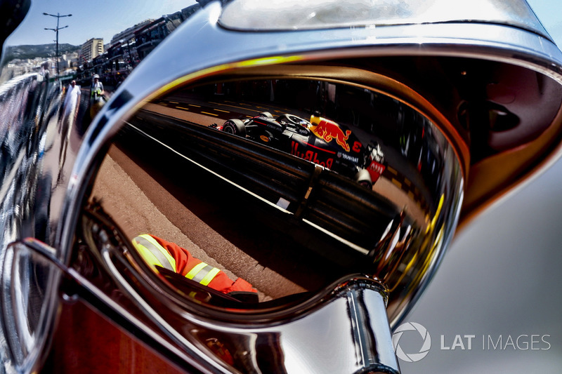 A reflection of the Daniel Ricciardo Red Bull Racing RB14 in the visor of a fire marshal