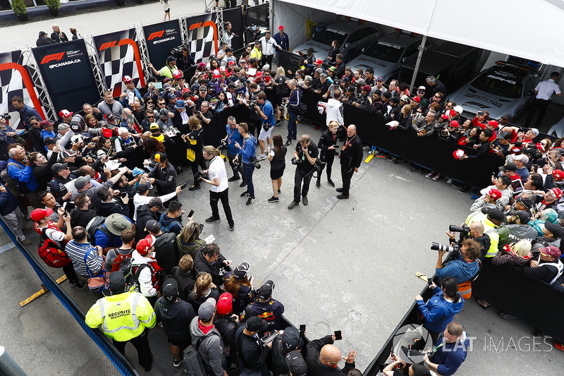 Fernando Alonso, McLaren, Carlos Sainz Jr., Renault Sport F1 Team, and Stoffel Vandoorne, McLaren, sign autographs for fans. Photographers, including Andy Hone, are among the melee in the enclosure