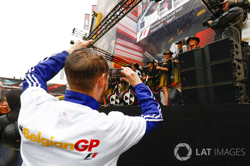 A fan takes a picture of the Grid Girls on stage in the F1 Fanzone