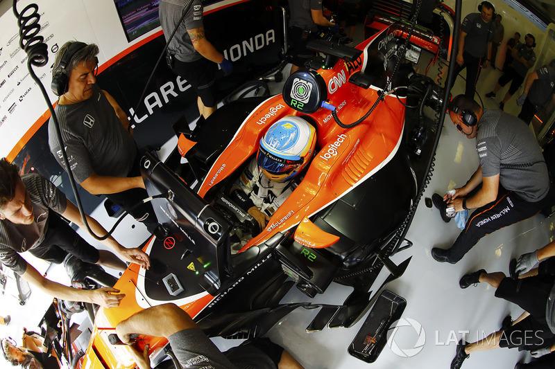 Fernando Alonso, McLaren, es atendido por mecánicos en su garaje