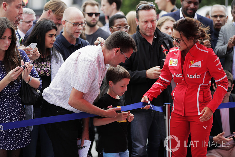 A young fan is invited under the barrier for a closer look at the activities by Ferrari promotional staff