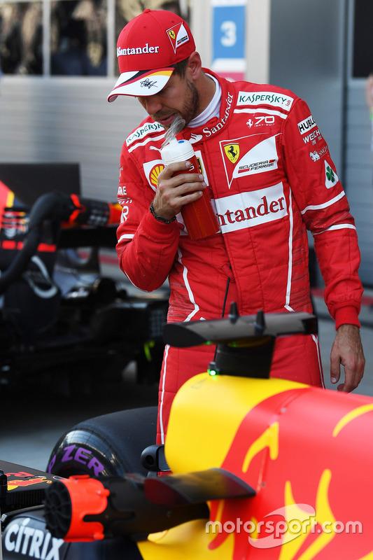 Pole sitter Sebastian Vettel, Ferrari looks at the Red Bull Racing RB13 in parc ferme
