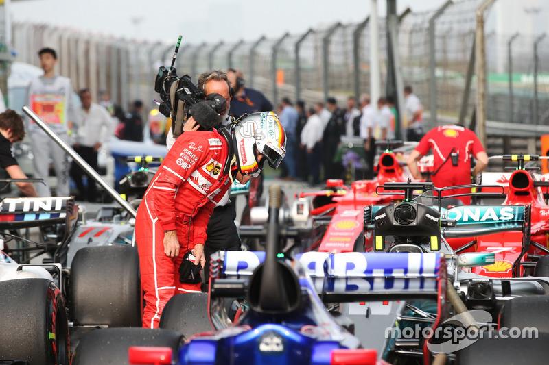 Sebastian Vettel, Ferrari, examines a Mercedes AMG F1 W08 in parc ferme