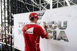 Kimi Raikkonen, Ferrari, signs an autograph on stage