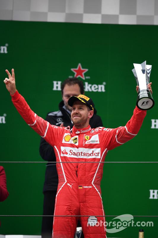 Sebastian Vettel, Ferrari celebrates on the podium with the trophy