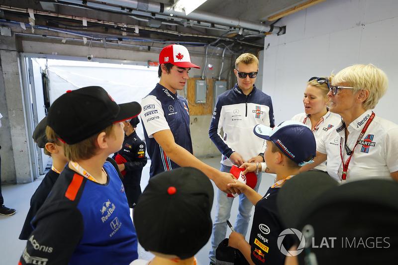 Lance Stroll, Williams Racing, and Sergey Sirotkin, Williams Racing, meet grid kids as PR Anne Brads