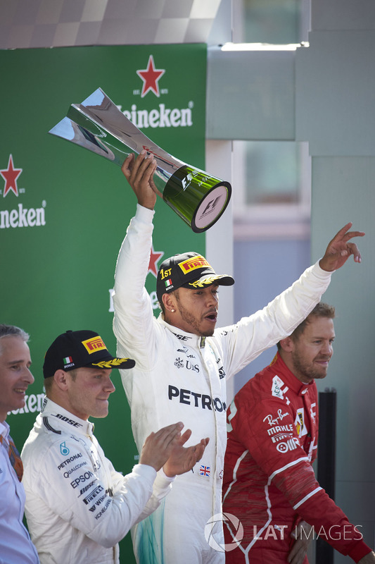 Second place Valtteri Bottas, Mercedes AMG F1, applauds as Race winner Lewis Hamilton, Mercedes AMG F1, raises the winners trophy