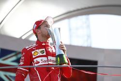 Third place Sebastian Vettel, Ferrari, kisses his trophy