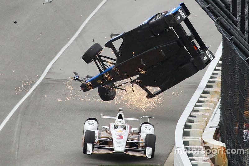 Choque de Scott Dixon, Chip Ganassi Racing Honda, Helio Castroneves, Team Penske Chevrolet, maneja por debajo