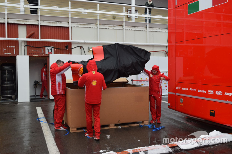 Ferrari team member get the new engine cover