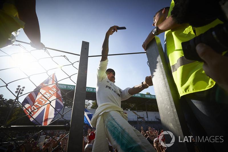 Lewis Hamilton, Mercedes AMG F1, takes a photo, fans