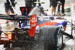 Water sprays from the rears of Carlos Sainz Jr., Scuderia Toro Rosso STR12, in the pit lane
