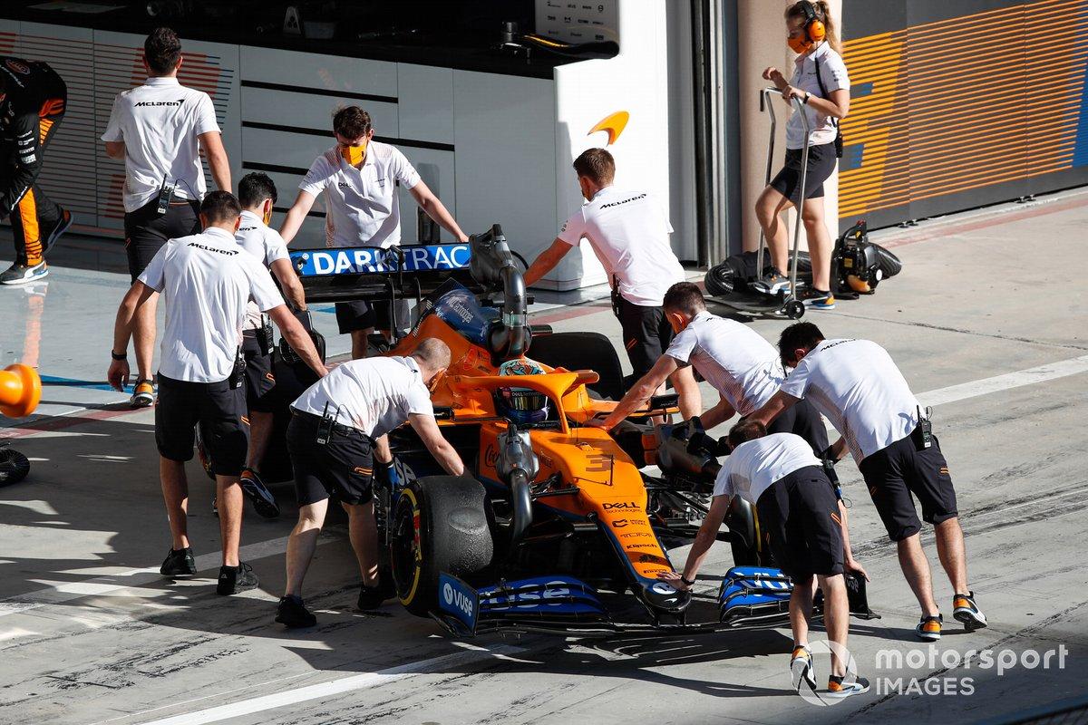 Mechanics push Daniel Ricciardo, McLaren MCL35M, back into the garage