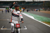 Jenson Button, McLaren, gets in the spirit of a bicycle-related promotional event