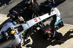 The Lewis Hamilton, Mercedes AMG F1 W08, is attended to by mechanics in the pit lane