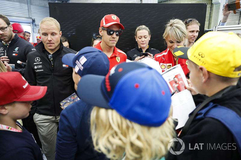 Valtteri Bottas, Mercedes AMG F1, y Sebastian Vettel, Ferrari, firma autógrafos para niños