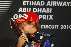 New world champion Sebastian Vettel, Red Bull Racing RB6 Renault kisses his trophy on the podium