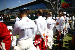 The drivers join the Grid Kid for the national anthem