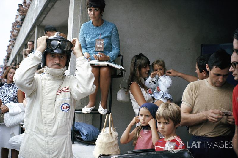 1967 - Graham Hill se prépare dans les stands, entouré par sa famille : sa femme Bette Hill et une nounou qui s'occupe des trois enfants, dont Damon Hill