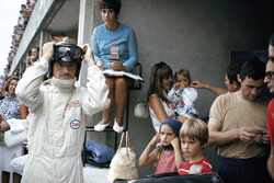 Graham Hill prepares for racing in pits, surrounded by his family: his wife Bette Hill and a nanny who looks after the three children - later F1 World Champion Damon front right hand