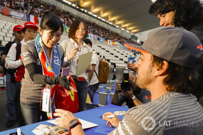 Fernando Alonso, McLaren, signs an autograph