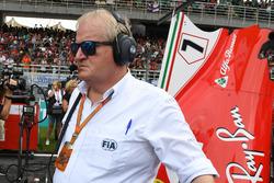 Технический делегат FIA Джо Бауэр наблюдает за механиками Ferrari возле автомобиля SF70H Кими Райкконена